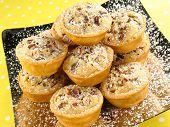 stock photo of confectioners  - Pecan tarts with a light sprinkle of confectioner - JPG