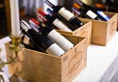 stock photo of bordeaux  - Wine bottles in wooden boxes are on the table restaurant - JPG