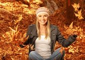 Picture of happy blonde girl having fun in autumn woods, pretty woman throwing up dry autumnal leave