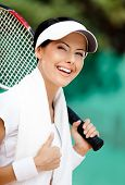 Successful female tennis player with towel on her shoulders. Active pastime