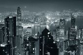 picture of skyscrapers  - Hong Kong city skyline at night with Victoria Harbor and skyscrapers illuminated by lights over water viewed from mountain top in black and white - JPG