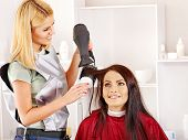 Woman at hairdresser with hairdryer.