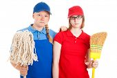 Two serious looking teenage girls, dressed in uniforms for menial jobs and holding a broom and mop.