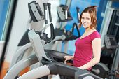 smiling fitness woman training legs muscles exercises at cardio simulator treadmill machine in gym
