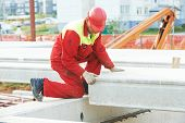 stock photo of millwright  - builder worker in safety protective equipment installing concrete floor slab panel at building construction site - JPG