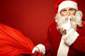 foto of shhh  - Portrait of Santa Claus with huge red sack keeping forefinger by his mouth and looking at camera - JPG
