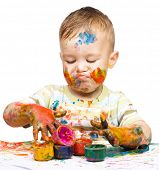 Portrait of a cute little boy messily playing with paints while making funny grimace, isolated over