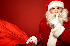 stock photo of shhh  - Portrait of Santa Claus with huge red sack keeping forefinger by his mouth and looking at camera - JPG
