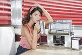 stock photo of jukebox  - Beautiful young woman drinking shake in a diner - JPG