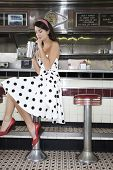 image of diners  - Full length side view of a young woman drinking shake at the diner counter - JPG