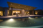 stock photo of electricity  - Luxurious and modern house with swimming pool at night - JPG