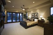 stock photo of master bedroom  - Dark wood furniture in bedroom with ceiling fan - JPG