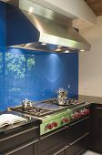 Blue backsplash and stainless steel vent hood in modern kitchen