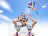 stock photo of shoulders  - happy little girl on his father shoulder with colorful kite - JPG