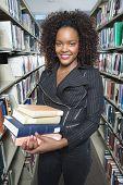 stock photo of shelving unit  - Female University student holding books in library portrait - JPG