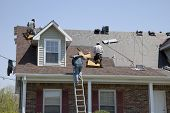 stock photo of shingles  - Roofers replacing damaged shingles after storm with very high winds came through over night - JPG
