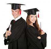 stock photo of white gown  - Two happy graduating students isolated on white - JPG