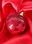 Beautiful Christmas ball on red satin cloth
