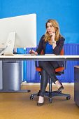stock photo of stressless  - Young woman sitting behind a large screen in an office - JPG