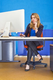foto of stressless  - Young woman sitting behind a large screen in an office - JPG