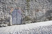 foto of cobblestone  - Ancient door by cobblestone street - JPG