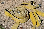 stock photo of firehose  - Firehose lying in the sand at a beach - JPG