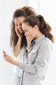 foto of two women taking cell phone  - Two women take pictures with your phone - JPG