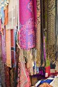 UAE, Dubai, colourful pashminas and fabrics for sale at Bur Dubai souq poster