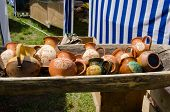 stock photo of trough  - painted clay jugs lying in wooden trough at village market - JPG