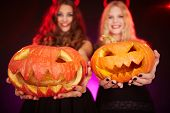 picture of antichrist  - Two happy females holding carved Halloween pumpkins - JPG