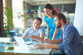 pic of gathering  - Group of three successful business partners in casual discussing data in laptop at meeting in office - JPG