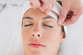 foto of eyebrows  - Close up of a hand waxing beautiful woman - JPG
