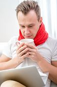 foto of rhinitis  - Ill man suffering from rhinitis sitting on the couch with red scarf and cup with hot drink at home - JPG