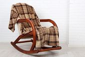 image of floor covering  - Rocking chair covered with plaid on wooden floor near the brick wall background - JPG