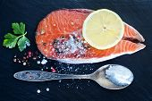 picture of salmon steak  - raw salmon steak with spice on the black board - JPG