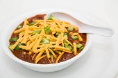 stock photo of poblano  - A white bowl of chilli with meat and beans and green poblano chile peppers topped with shredded cheddar cheese  - JPG