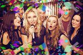 foto of karaoke  - Happy friends singing karaoke together against flying colours - JPG