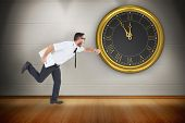 image of running-late  - Geeky young businessman running late against room with wooden floor - JPG