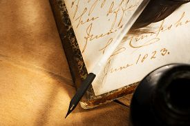 stock photo of inkpot  - Old book with feather and inkpot in closeup - JPG
