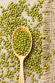 picture of mung beans  - Wooden spoon with heap of raw green organic mung beans on vintage textile background - JPG