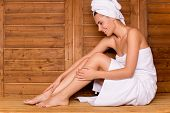picture of sauna woman  - Attractive young woman wrapped in towel relaxing in sauna and smiling - JPG