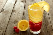 stock photo of glass water  - Nutritious fruit water with lemon and raspberries in a glass against a wood background - JPG