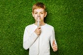 stock photo of inhalant  - Portrait of a boy breathing through inhaler mask over spring green grass background - JPG