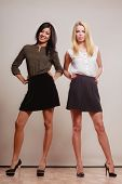 stock photo of short skirt  - Two young women caucasian and african in trendy short black skirts posing in full length studio portrait on gray - JPG