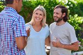 stock photo of gathering  - friends chatting outdoors at garden party gathering with cocktail wine drinks - JPG