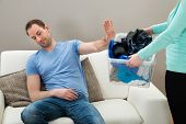image of dirty-laundry  - Man On Sofa Ignoring Dirty Clothes Hold By A Woman - JPG