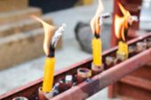 image of worship  - blurry defocused image of flame of candle for worship in thailand temple for background - JPG