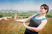 picture of sportswear  - Beautiful plus size woman in sportswear refusing junk food outdoor - JPG