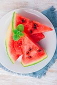 image of watermelon slices  - sliced watermelon with mint leaf on a white plate - JPG