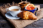stock photo of croissant  - Cup of coffee with milk grapefruit and fresh croissant - JPG